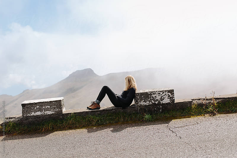 Woman enjoying the view up in the mountains and takes a rest by Denni Van Huis for Stocksy United