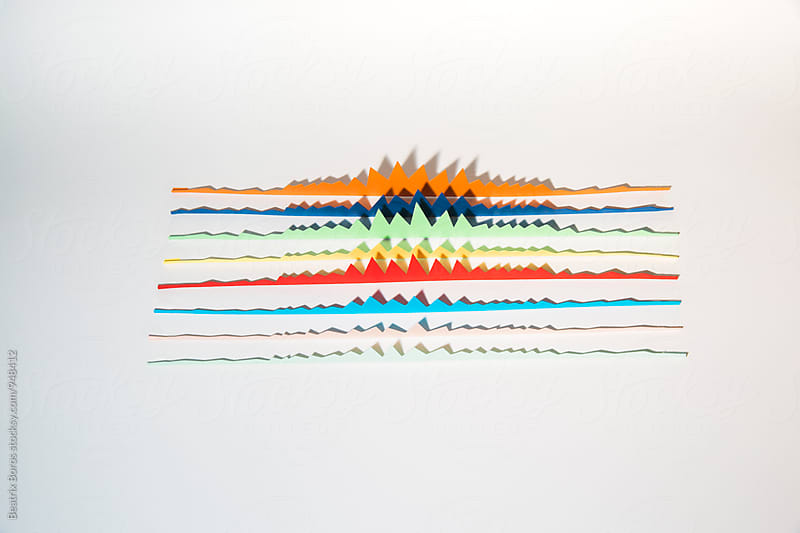 Charts cut out of paper put behind each other on striped background for measure by Beatrix Boros for Stocksy United