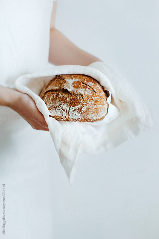 Woman holding whole grain bread by Ellie Baygulov for Stocksy United