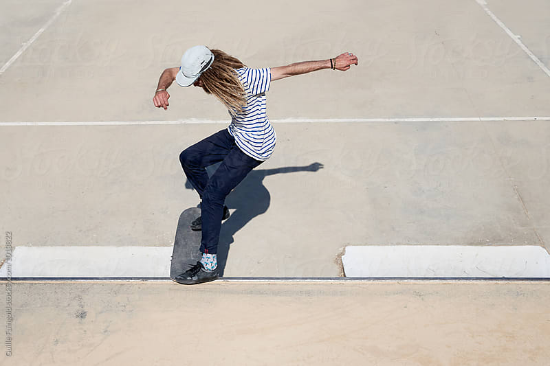 Long-haired guy performing trick on skateboard by Guille Faingold for Stocksy United