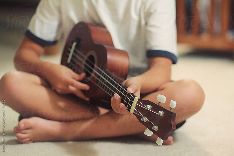 Young boy plays the Ukulele sitting on carpet by Monica Murphy for Stocksy United