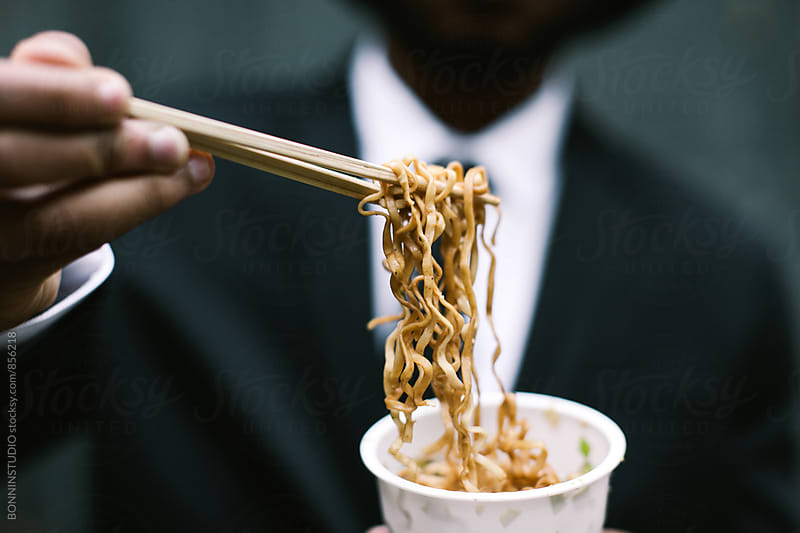 Closeup of a man eating noodles outside. by BONNINSTUDIO for Stocksy United