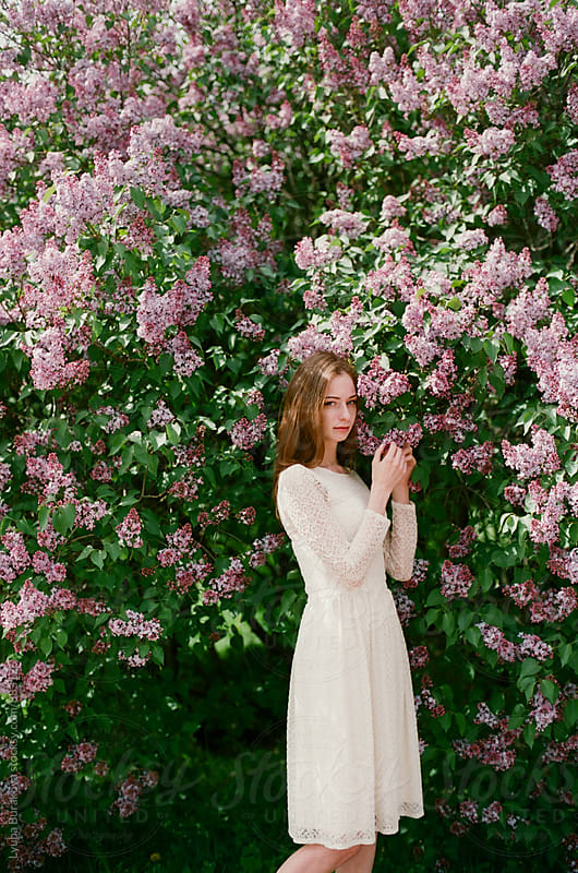 Young woman posing among lilac in blossom by Lyuba Burakova for Stocksy United