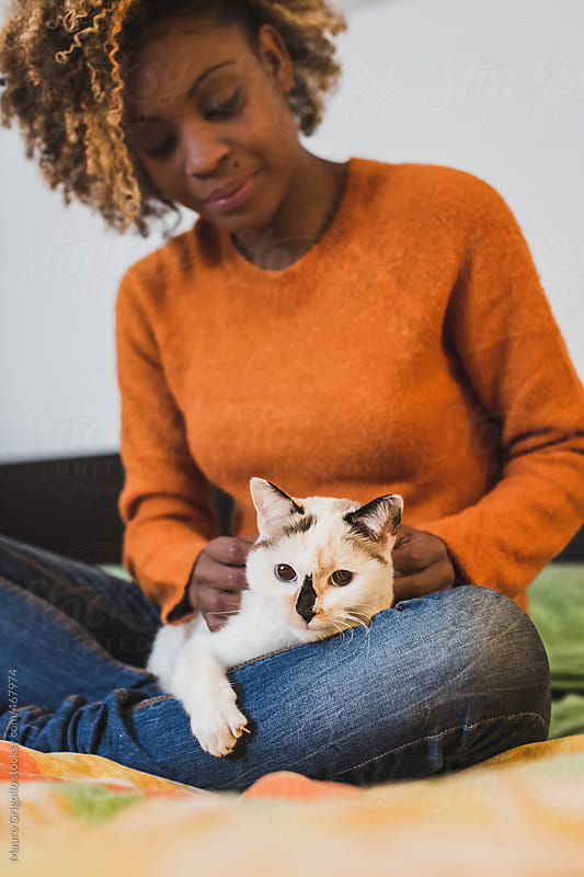 Woman with her cat at home by Mauro Grigollo for Stocksy United