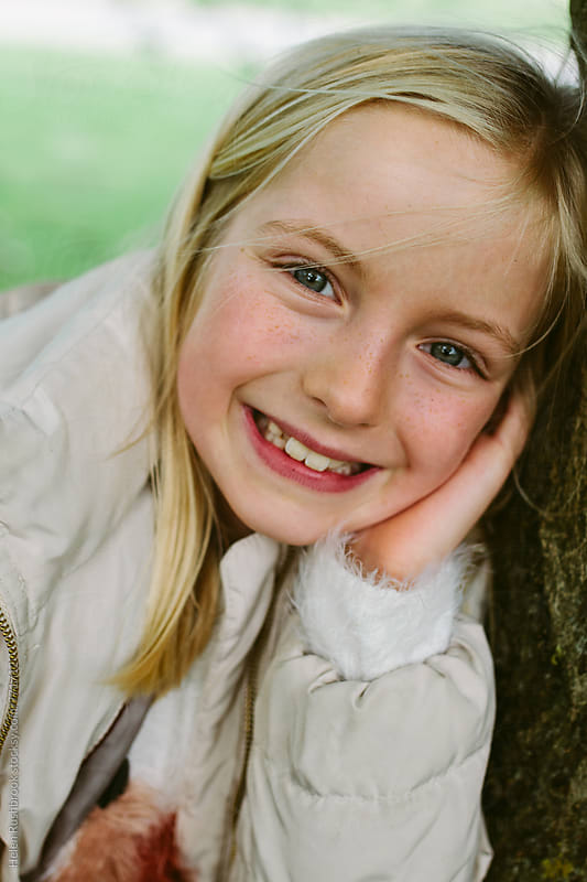 Portrait of a smiling little girl outdoors by Helen Rushbrook for Stocksy United