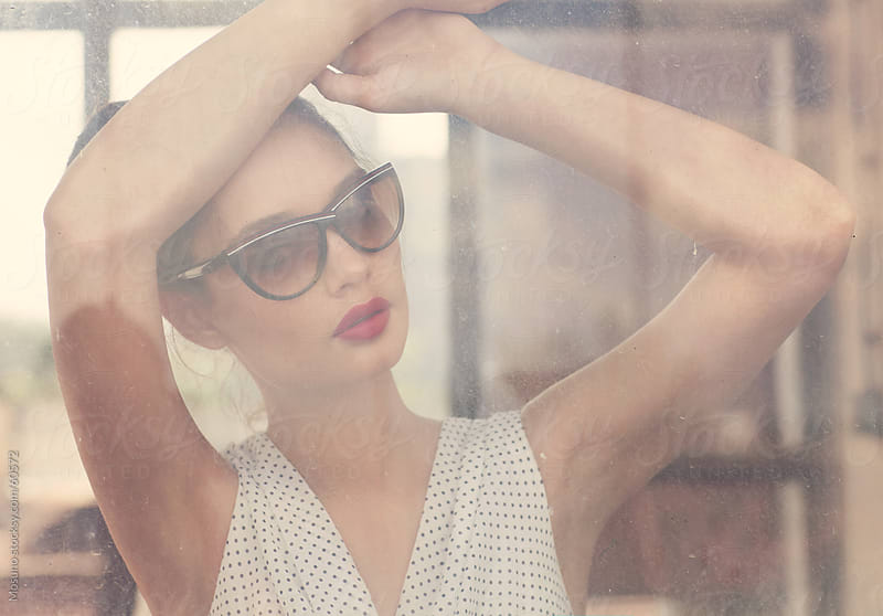 Fashion model looking through the old window. by Mosuno for Stocksy United