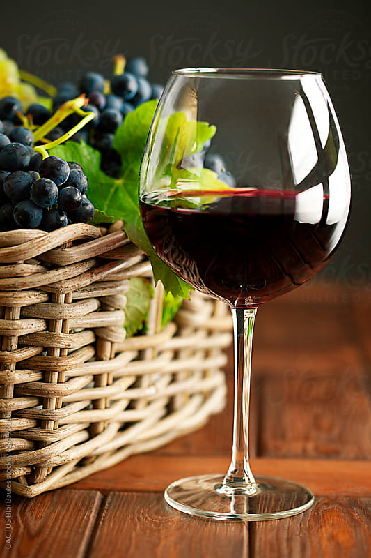 Red wine glass and wicker basket of grapes by CACTUS Blai Baules for Stocksy United