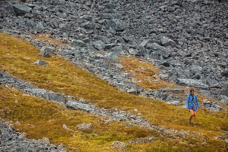 Hiker Descending a Rocky Grassy Mountain Side by Willie Dalton for Stocksy United