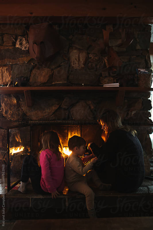 Young mom getting cozy and warm with kids by the fireplace in winter by Rob and Julia Campbell for Stocksy United