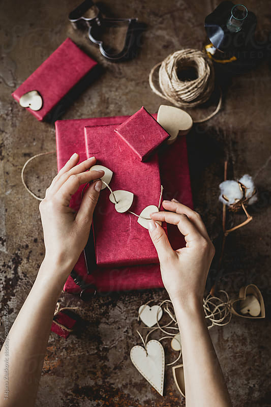 Hands wrapping gifts for Valentine's Day by Tatjana Ristanic for Stocksy United