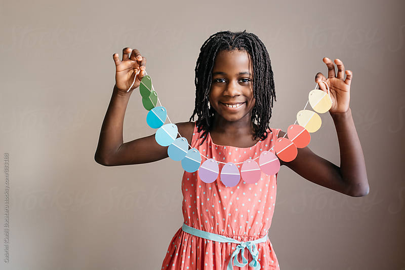 African American girl holding an Easter egg garland by Gabriel (Gabi) Bucataru for Stocksy United