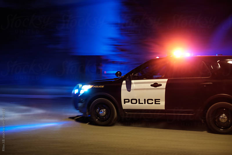 A police vehicle driving fast with red & blue lights flashing. by Riley Joseph for Stocksy United