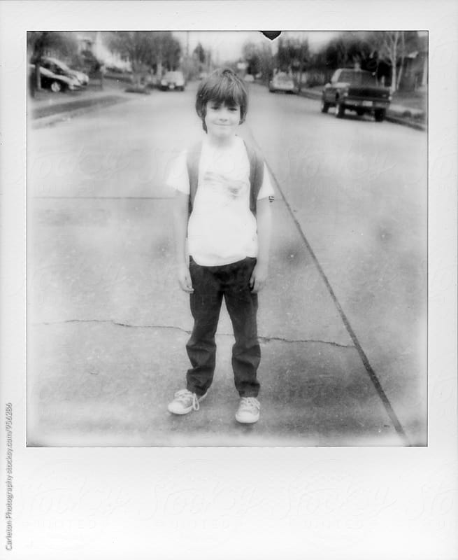 Seven year old boy stands in the middle of the street by Carleton Photography for Stocksy United