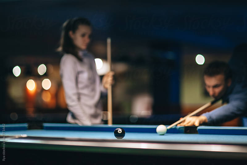 Couple playing pool billiard game, young out of focus man taking a shot. by Ilya for Stocksy United