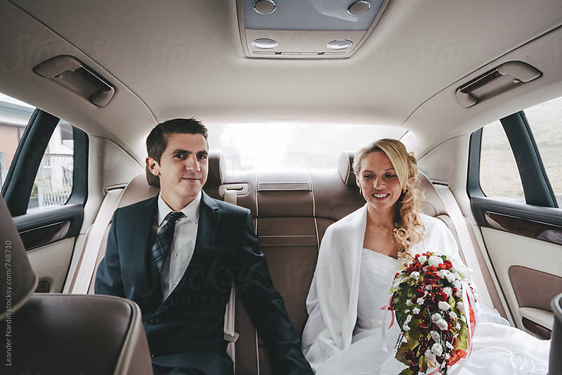 bridal couple on the backseat of a wedding car by Leander Nardin for Stocksy United