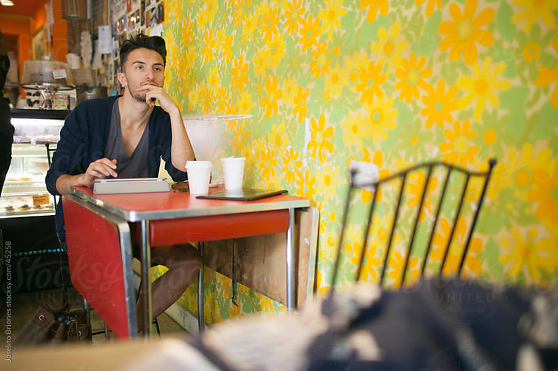 Young Man Using Tablet Device in a Cafe by Joselito Briones for Stocksy United