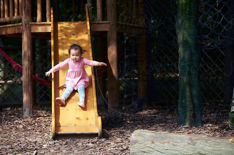 little asian girl on slide by Bo Bo for Stocksy United