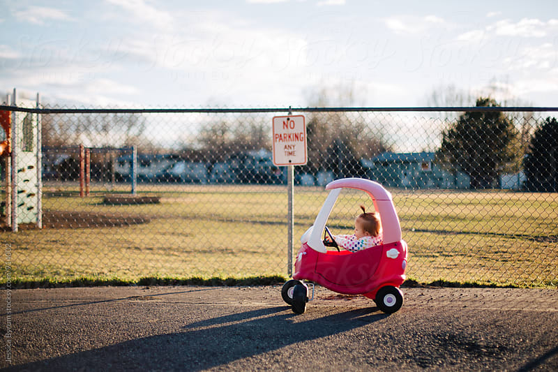 Toddler girl in pink car by fence by Jessica Byrum for Stocksy United