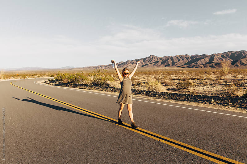 Pregnant Blonde Woman Walking In Middle Of Desert Highway With Arms Raised In Happiness by Luke Mattson for Stocksy United