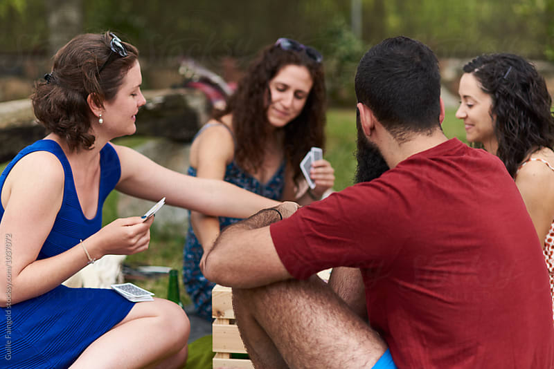 Friends playing poker in garden by Guille Faingold for Stocksy United