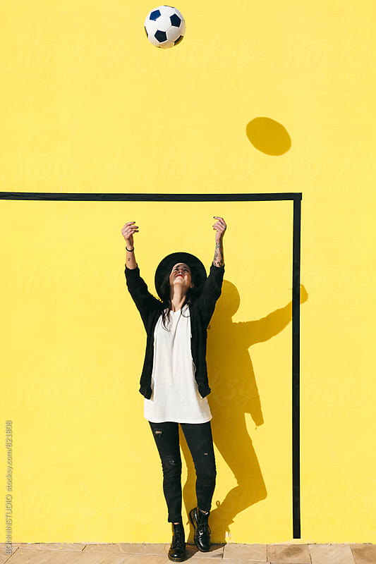 Alternative woman playing with soccer ball in front of a yellow wall. by BONNINSTUDIO for Stocksy United