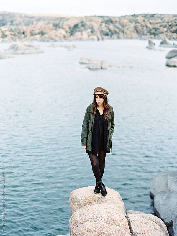 Woman standing on rock over lake by Daniel Kim Photography for Stocksy United