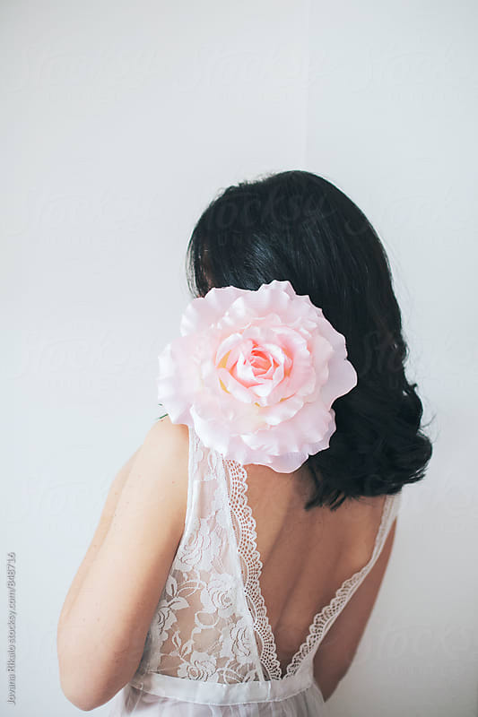 Back view of  a young woman holding a big flower by Jovana Rikalo for Stocksy United