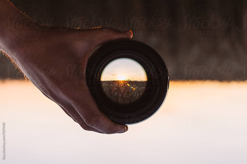 View through spyglass lens to the sunset on the dry field by Ilya for Stocksy United