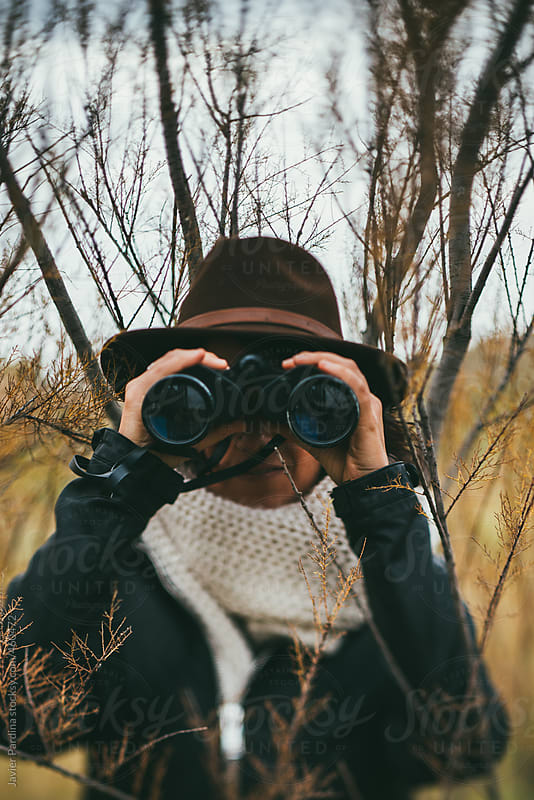 woman exploring  with binoculars by Javier Pardina for Stocksy United