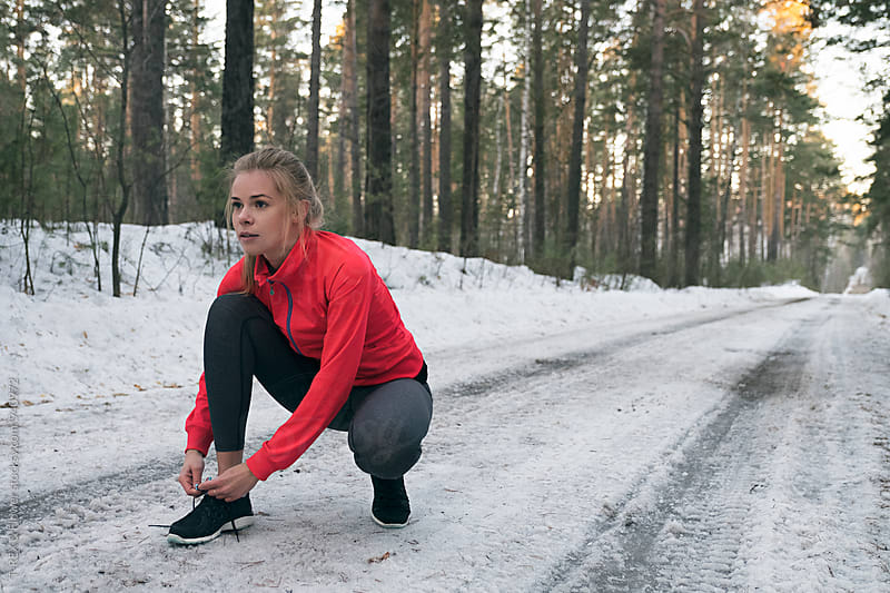Young sportswoman tying up laces on sneakers on snowy road by Danil Nevsky for Stocksy United