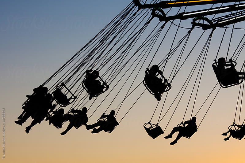 kids in silhouette on wave swinger by Thomas Hawk for Stocksy United