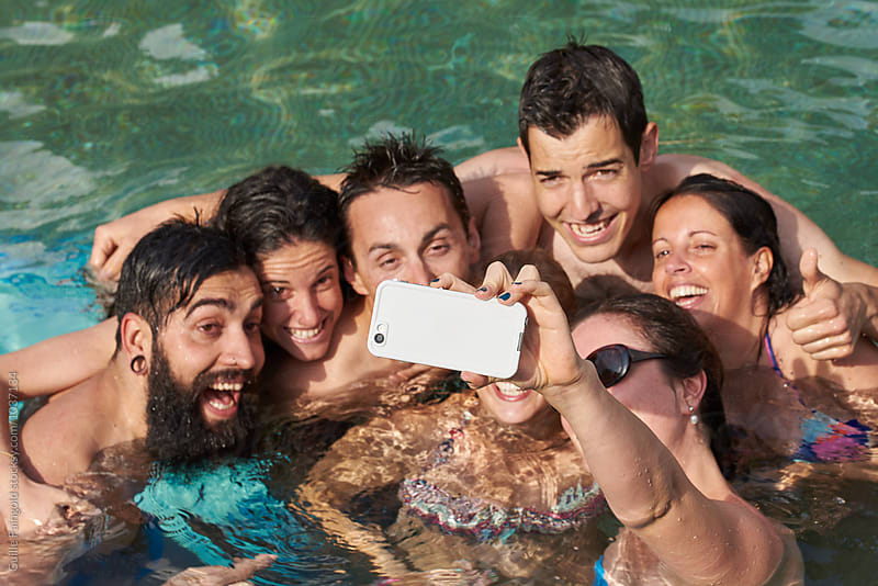 Happy friends taking selfie on cell in pool by Guille Faingold for Stocksy United