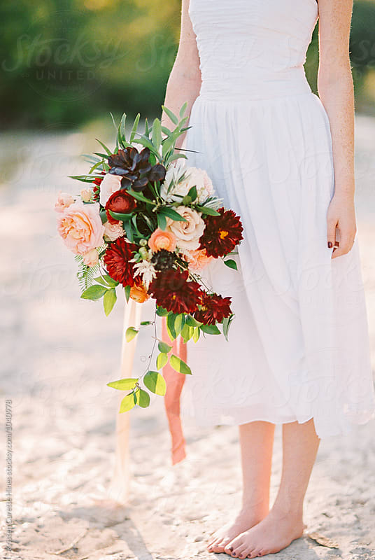 A woman standing bare foot outdoors holding a large beautiful flower bouquet.  by Kristen Curette Hines for Stocksy United