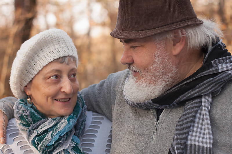 Senior couple talking to each other outdoors in the forest by Beatrix Boros for Stocksy United