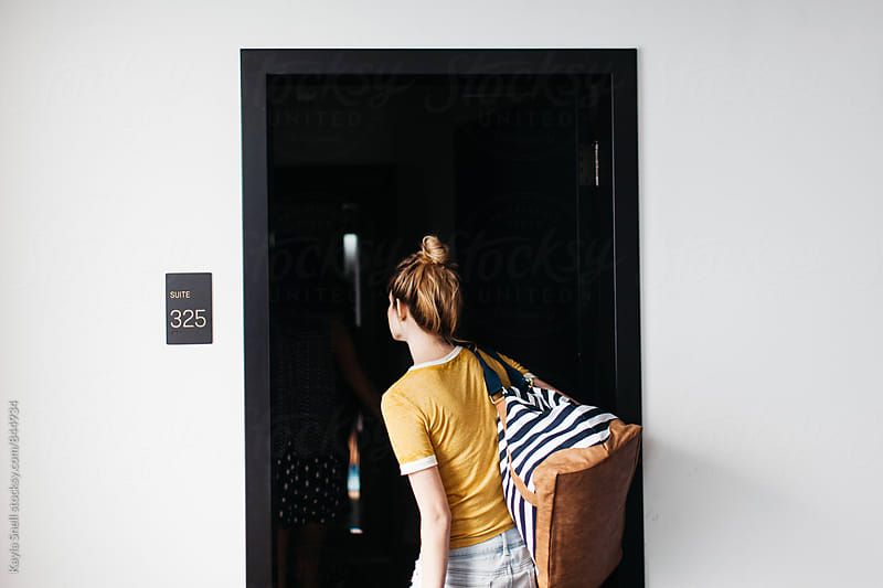 Woman walking into hotel room by Kayla Snell for Stocksy United