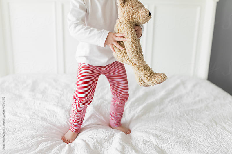 Young girl wearing red and white striped pajamas holding teddy bear by Amanda Worrall for Stocksy United