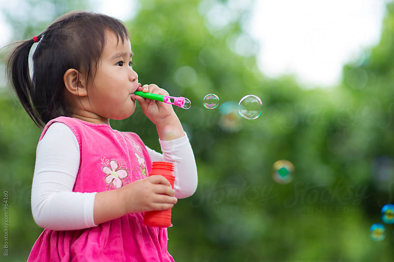lovely little asian girl blowing bubble  by Bo Bo for Stocksy United