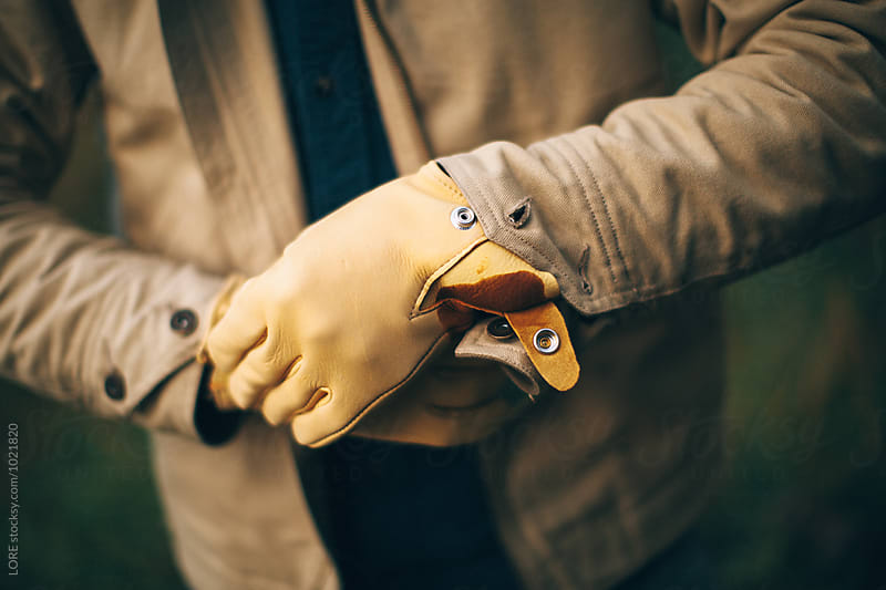 One adult male puts on leather gloves in preparation by LORE for Stocksy United