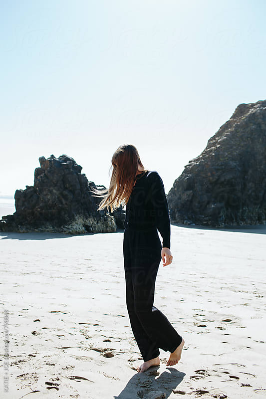 Girl standing on a beach with the wind in her hair by KATIE + JOE for Stocksy United