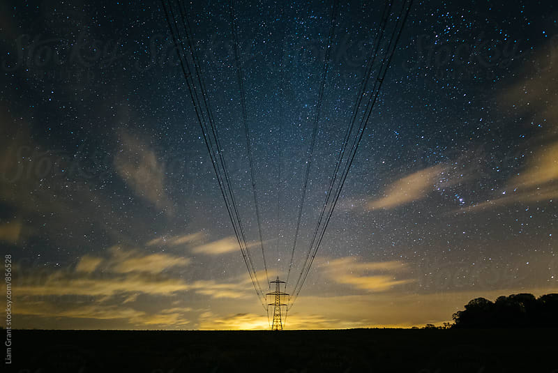 Electricity pylons, stars and clouds. West Acre, Norfolk, UK. by Liam Grant for Stocksy United