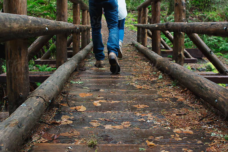 feet of couple walking across rustic pole bridge in mountains by Tana Teel for Stocksy United