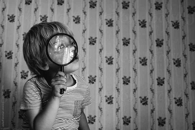 Child puts a magnifying glass close to his face and looks through. by Julia Forsman for Stocksy United