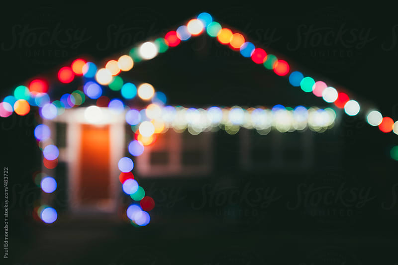 Colorful decorative Christmas lights outside home at night, blurred focus by Paul Edmondson for Stocksy United