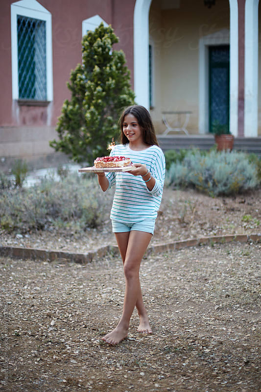 Young girl carrying a birthday cake by Miquel Llonch for Stocksy United
