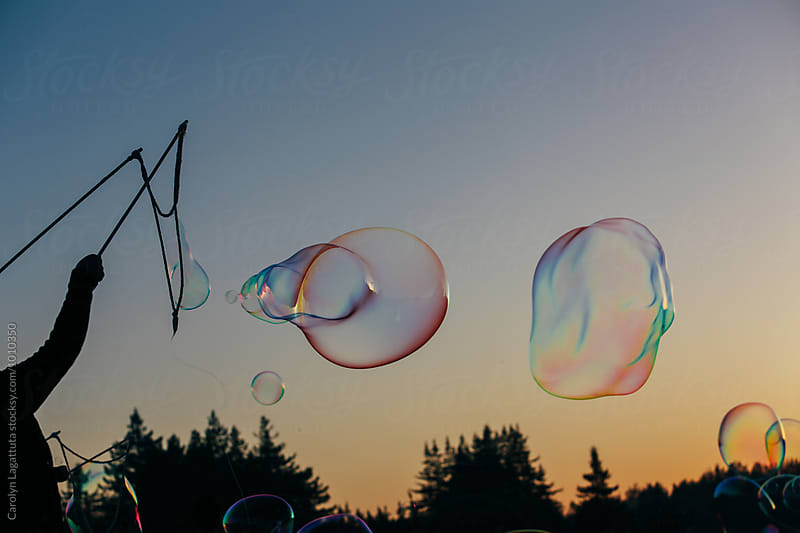 Person playing with large soap bubbles at sunset by Carolyn Lagattuta for Stocksy United