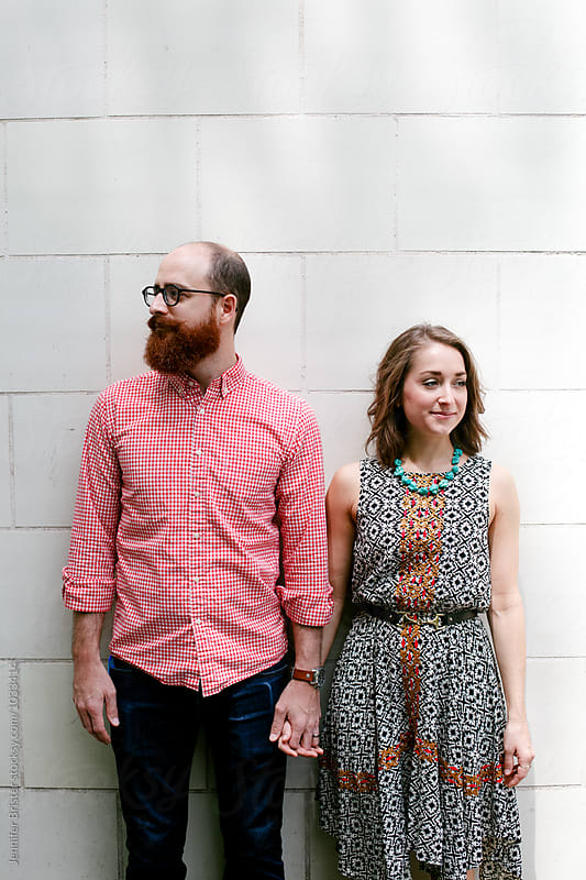 Couple stands against white background by Jennifer Brister for Stocksy United