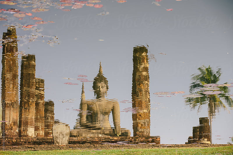 Reflection in a pond of Buddha statue by michela ravasio for Stocksy United
