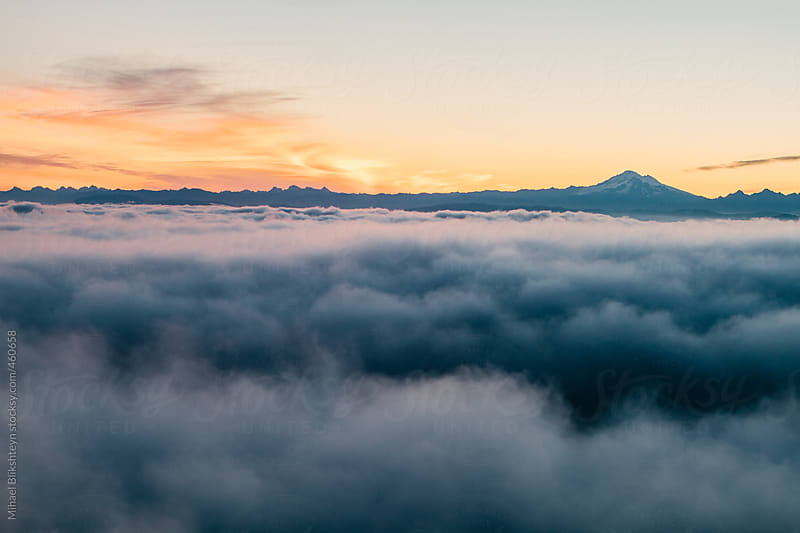 Aerial view of thick low clouds and mountains at sunrise by Mihael Blikshteyn for Stocksy United