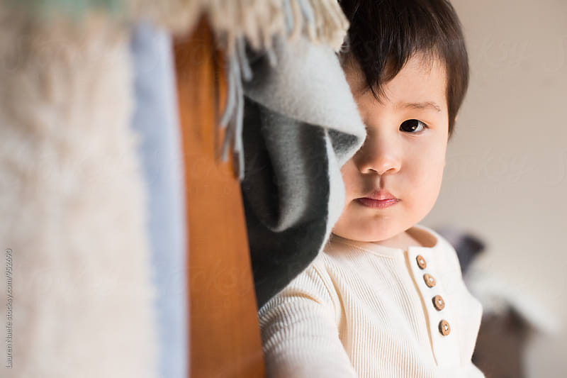 Toddler looking at camera from behind blanket by Lauren Naefe for Stocksy United