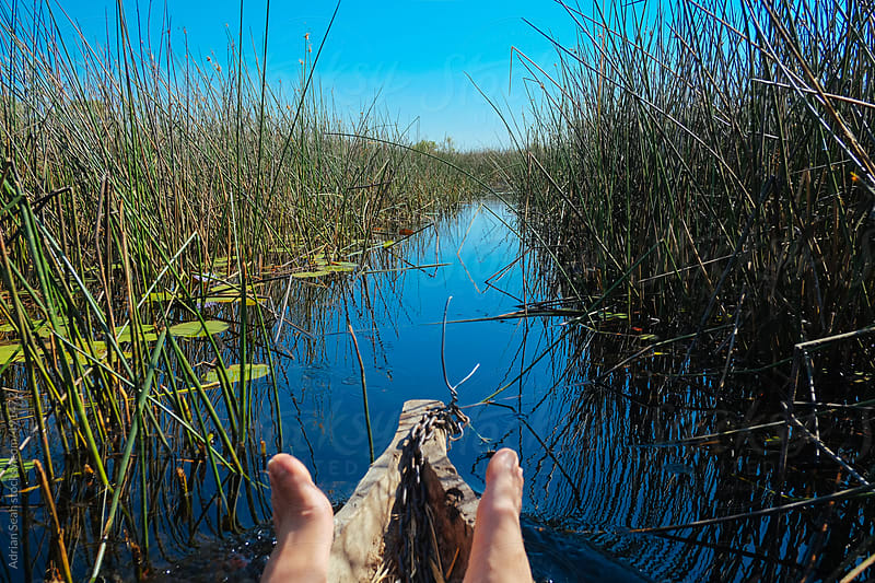 Relaxed feet in a wooden canoe on the Okavango Delta by Adrian Seah for Stocksy United
